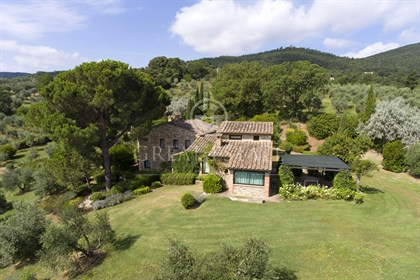 The farmhouse for sale is surrounded by a lush romantic gard...