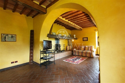 The farmhouse for sale is surrounded by a lush romantic garden where there are pergolas of