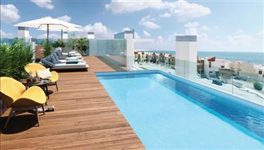 T2 em condomínio de luxo com piscina privada no topo do edifício, em frente à praia.