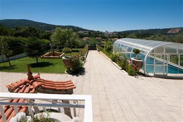 Moradia T4 com varanda coberta, jardim, piscina coberta, garagem, estufa e vistas panorâmicas numa l