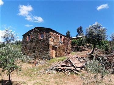 Terreno no meio da natureza com casas de pedra junto a ribeiro